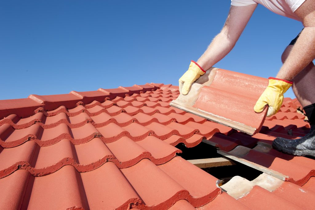 Roofer fixing roof tile