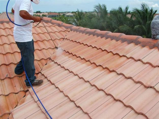 contractor cleaning house roof with high pressure hose